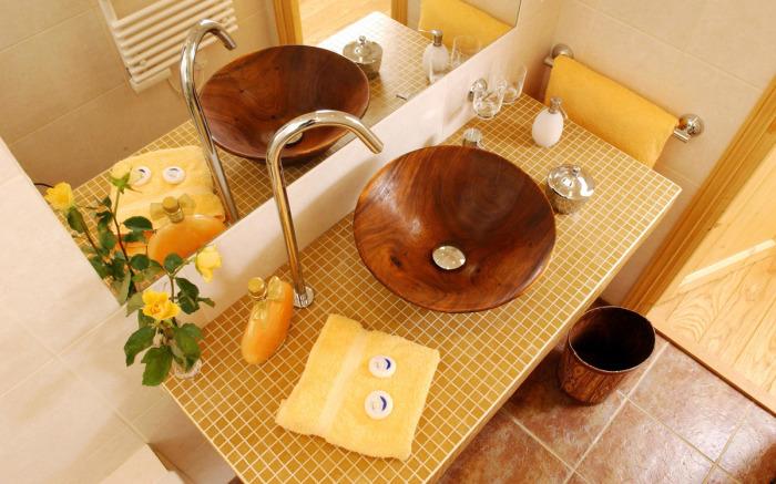 Раковина из темной породы древесины станет лучшим решением для ванной комнаты.