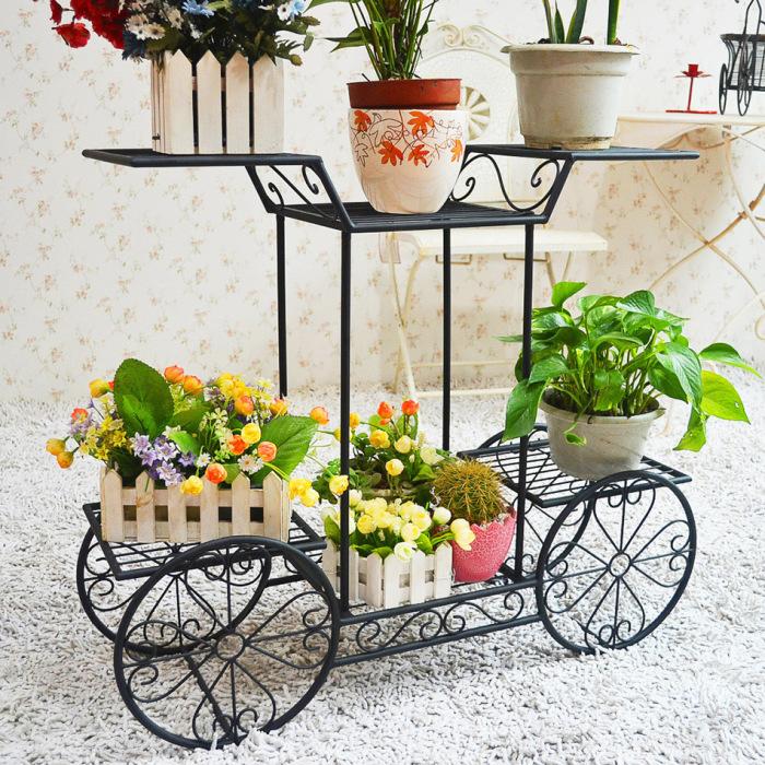 Оригинальная кованая металлическая подставка для цветов из прутьев с круглым сечением.