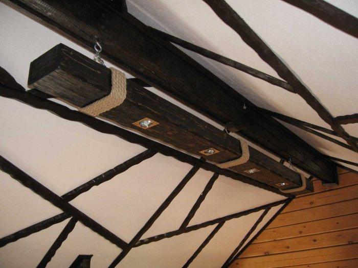Массивная деревянная балка, в которую встроены небольшие галогенные светильники.