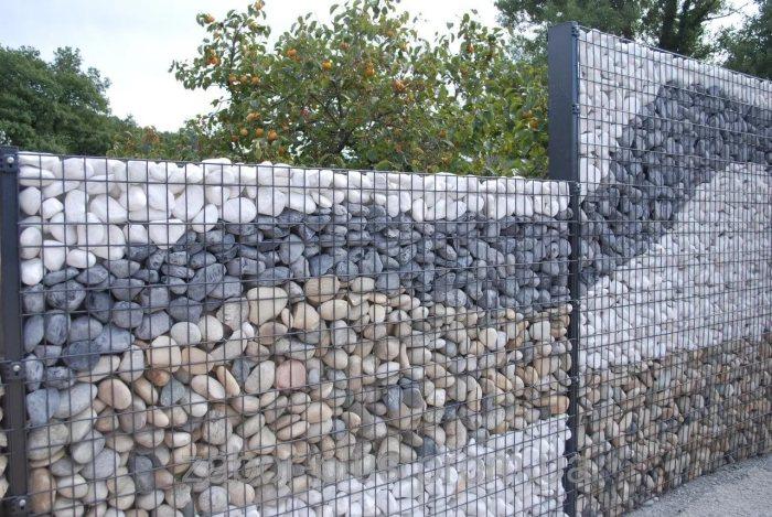 Необычное ограждение из габионых сеток, заполненных разноцветными камнями.