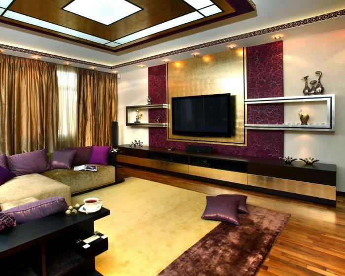 Современный интерьер гостиной комнаты в сочетании с золотой и фиолетовой гаммой.