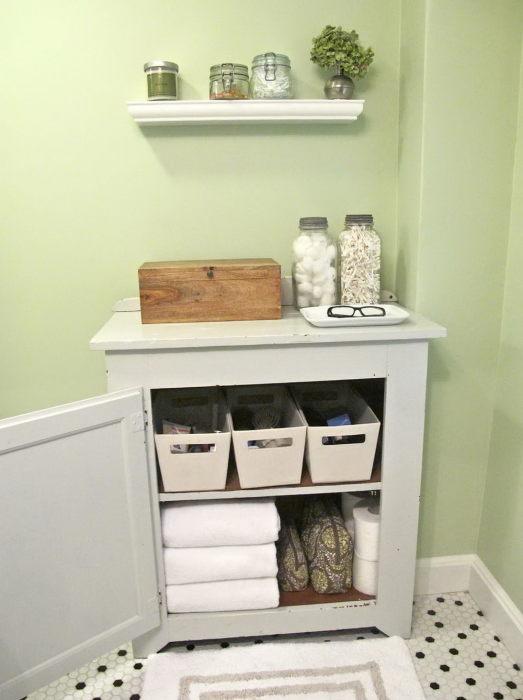 Старую прикроватную тумбочку можно использовать для хранения банных принадлежностей и моющих средств.