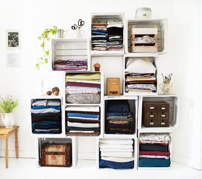 Небольшой стеллаж, сделанный из множества деревянных ящиков, покрашенных в белый цвет, может стать бюджетной альтернативой массивному и дорогому покупному шкафу.