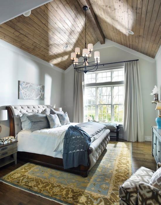 Спальная комната в загородном домике с необычной конструкцией потолка и панельным окном, которые позволят визуально расширить пространство в помещении.