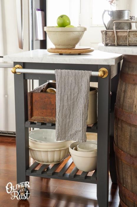 Небольшая деревянная кухонная тележка на колёсиках с двумя полочками, которые созданы для большей экономии пространства.