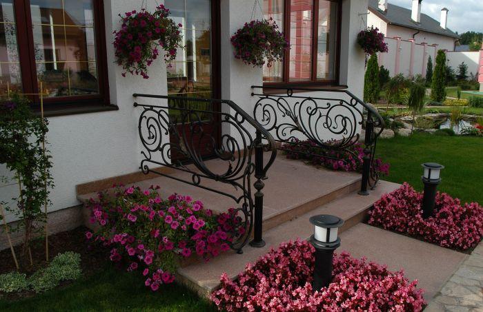 Притягивающая цветовая палитра цветника на крыльце у входа в дом.