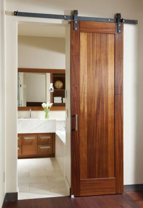 Традиционные деревянные межкомнатные двери с раздвижным механизмом - практичное решение для малогабаритной квартиры.