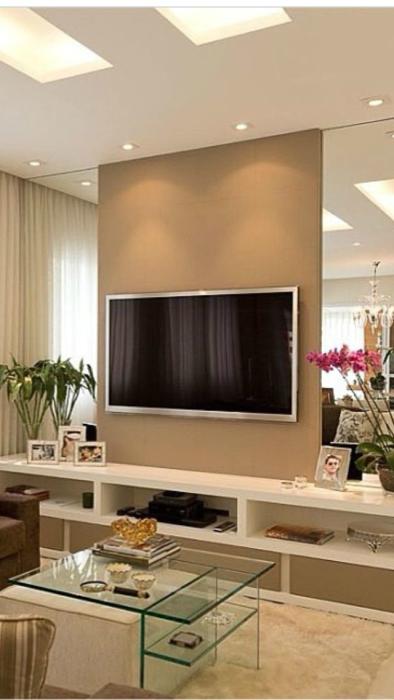 Зону для просмотра телевизора можно выделить благодаря простой гипсокартонной конструкции, обшитой по бокам зеркалами.