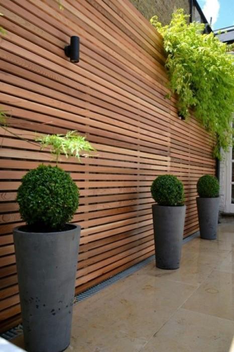 Простой панельный деревянный забор не только надежно защитит домовладение от посторонних глаз и незваных гостей, но и станет современным украшением загородного участка.