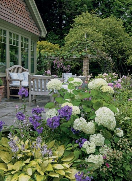Летнее патио с классической деревянной мебелью, украшенной изумительными полосатыми подушками, четырьмя невысокими скамейками и цветущими растениями.
