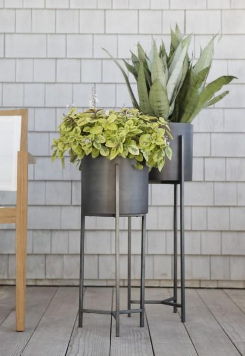 Кованая металлическая подставка, покрашенная в серый цвет.