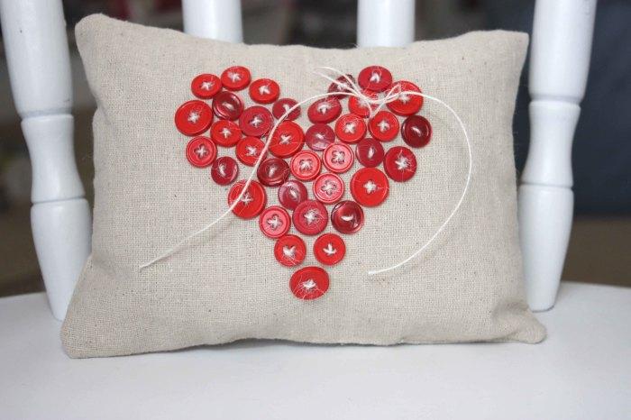 Рисунок в форме сердца созданный из простых пуговиц.