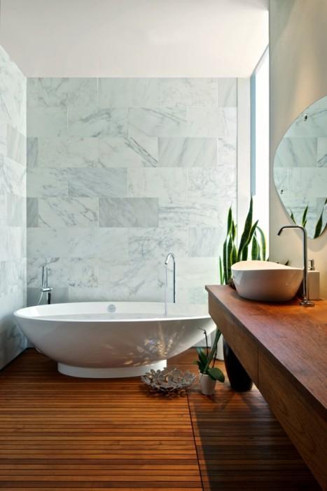 Удивительное сочетание деревянного паркета и искусственного мрамора в интерьере ванной комнаты.