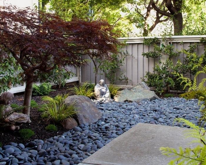 Каменная статуя Будды в центре композиции японского сада.