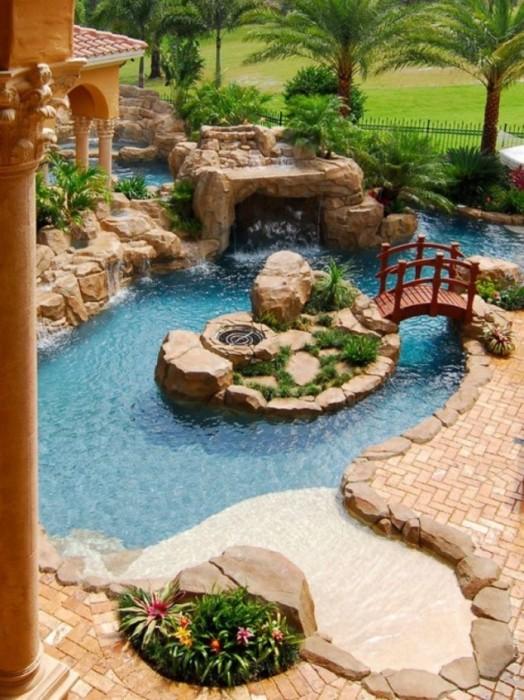 Восхитительный декоративный пруд с кристально чистой водой, огромными валунами, множеством каскадных водопадов и небольшим деревянным мостиком.
