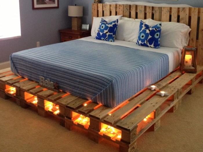 Каркас кровати, выполненный из множества деревянных поддонов в несколько рядов.