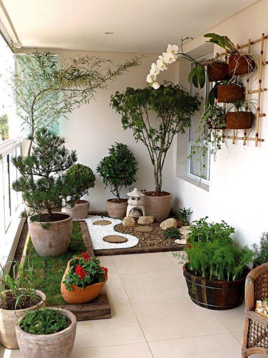 Сказочная композиция из гальки в декоративном саду на балконе загородного дома.