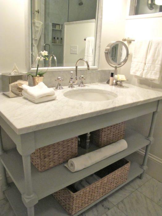 Если в ванной имеется свободное пространство под раковиной, его удобно задействовать для хранения полотенец и других банных принадлежностей.
