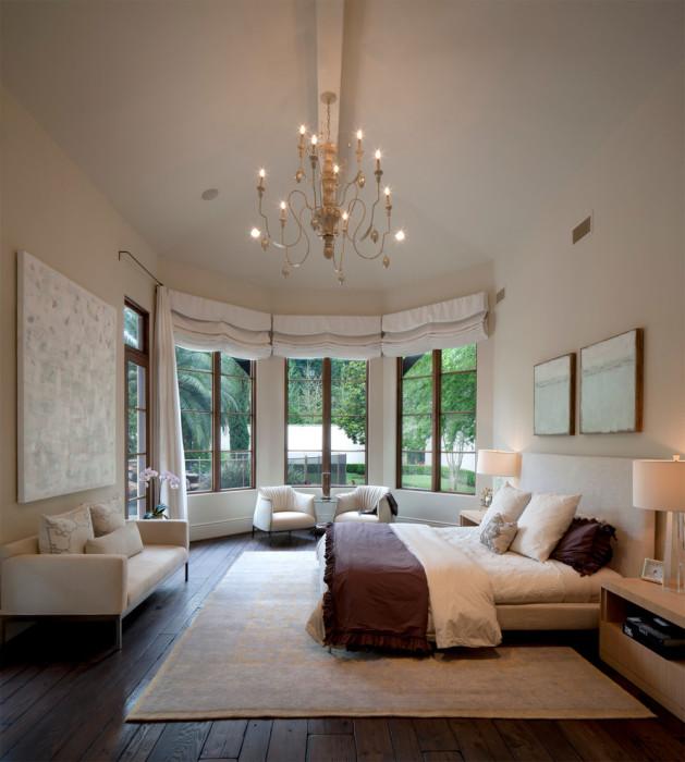 Просторная спальная комната необычной формы с большими панельными окнами.