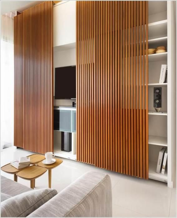 Необычная деревянная панельная перегородка, которая в любой момент позволит скрыть стеллаж и зону для просмотра телевизора.