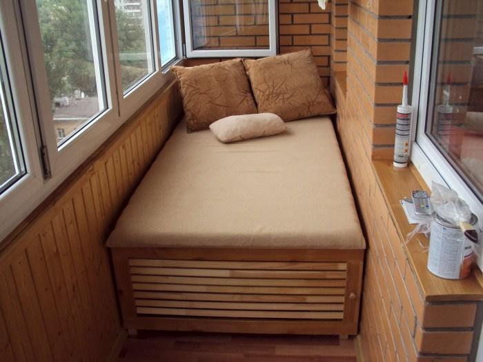 Небольшая застеклённая лоджия, оформленная с применением классической кирпичной кладки и панелей из светлой породы древесины.