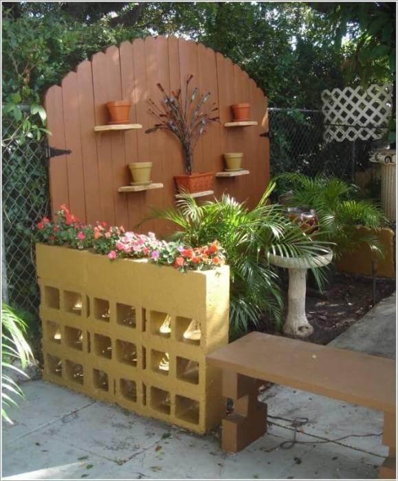 Покрашенную клумбу из шлакоблоков можно использовать для зонирования пространства на дачном участке.