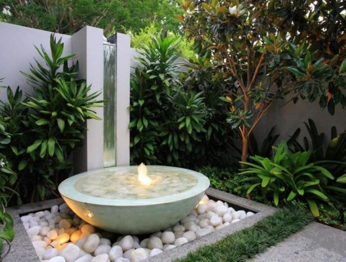 Керамический фонтан чашеобразной формы, стоящий на морских камнях.