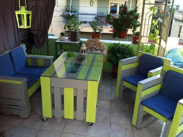 Яркая садовая мебель из старых деревянных поддонов, которая акцентным пятном выделяется на фоне общего дизайна лоджии.