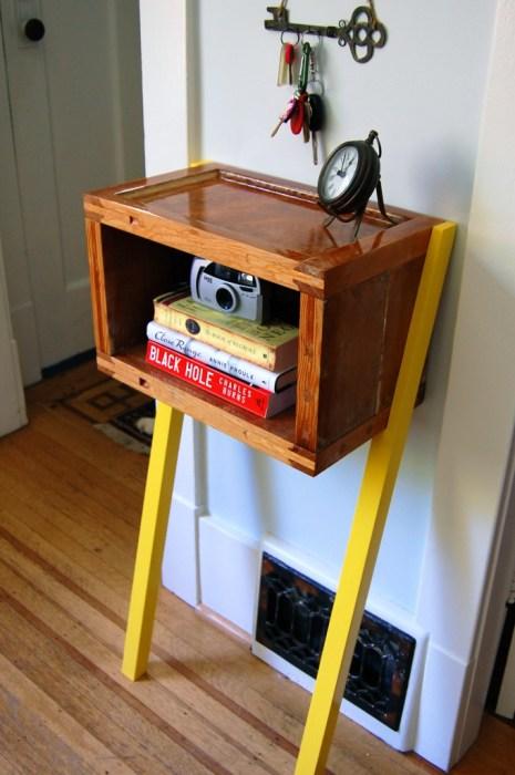 Старая деревянная коробка, которая выполняет роль небольшой полки для книг.