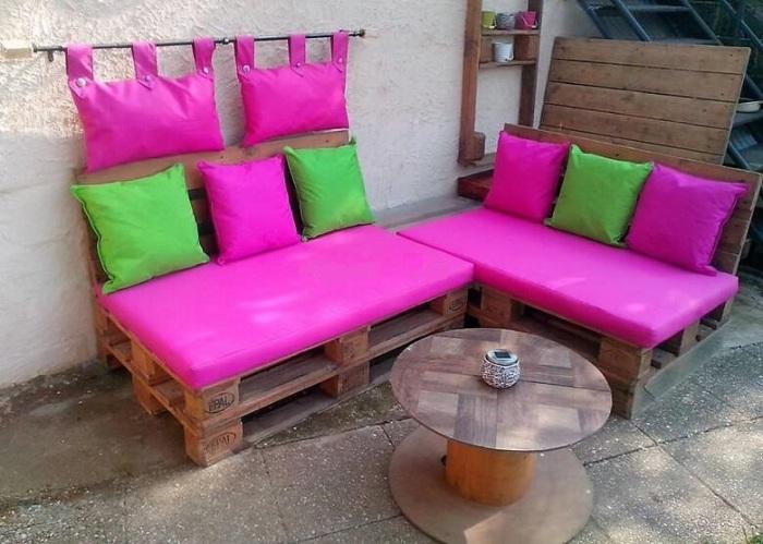 Из нескольких деревянных поддонов можно смастерить удобный диванчик, который станет настоящим украшением загородного дома.