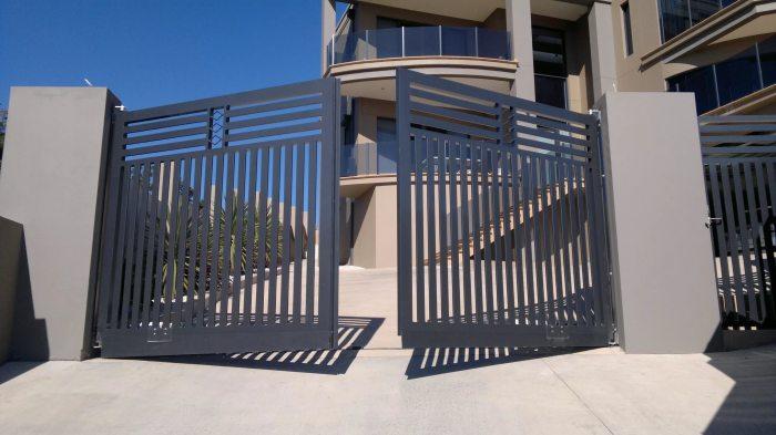 Современные металлические ворота и калитка на бетонных столбах.