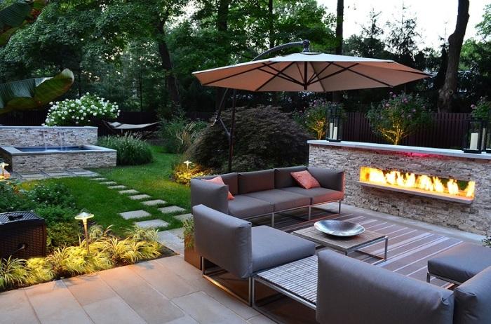 Оригинальный дизайн летнего патио с маленьким деревянным столиком, мягкими диванчиками, большим зонтом и местом для разведения огня.