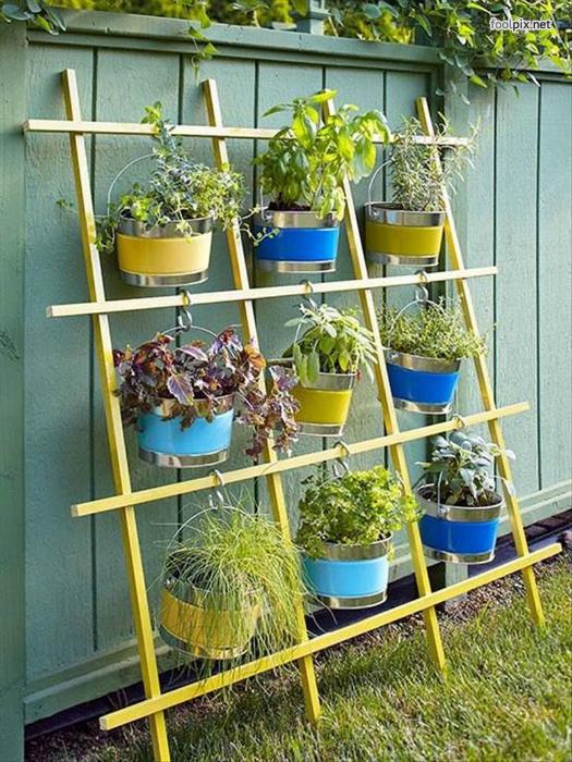Яркие металлические ведёрка-кашпо с растениями можно разместить на небольшой деревянной решетке.