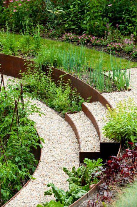 Садовая дорожка между грядок, выложенная мелкой галькой.