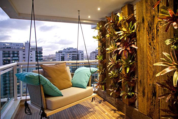 Открытая лоджия с небольшим вертикальным садом и оригинальным подвесным диванчиком.