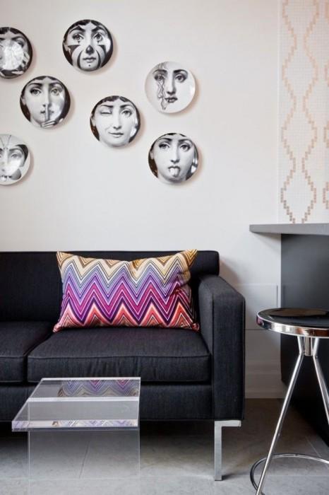 Контрастная подушка с яркими узорами и настенная декоративная посуда в интерьере гостиной.
