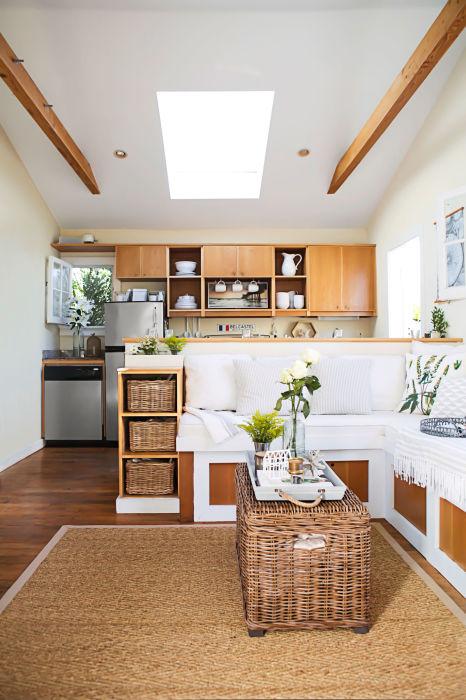 Гостиная комната, совмещённая с кухней с множеством декоративных элементов из натурального дерева.