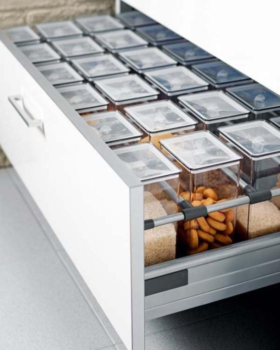 Шкаф с металлическими отсеками для хранения пластиковых контейнеров со специями.