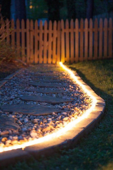 Садовая дорожка с неоновой подсветкой, которая создана из деревянных досок на фоне белой гальки.