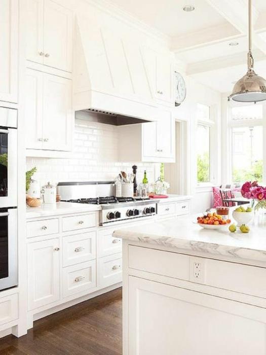 Нескучный интерьер небольшой светлой кухни с современной белой мебелью.