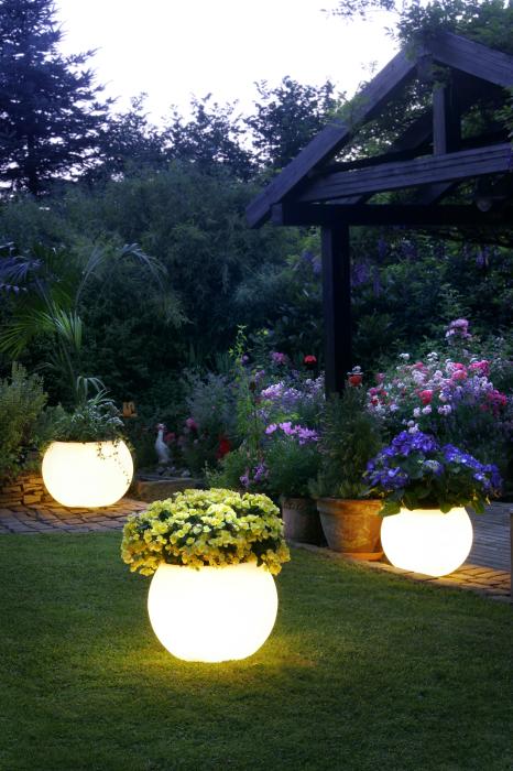 Садовый участок украшенный при помощи кашпо с необыкновенной подсветкой.