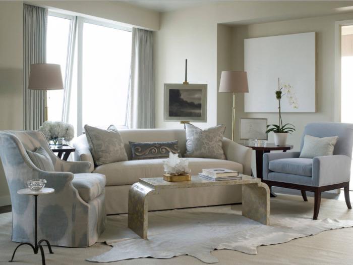 Гостиная комната в светлых тонах с шикарной мягкой мебелью, журнальным столиком из декоративного камня и классическим деревянным мольбертом.