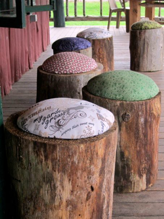 Обычные садовые табуреты из пней с яркими мягкими подушками.
