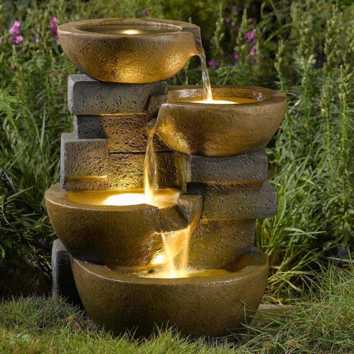 Небольшой каменный каскадный фонтан с яркой подсветкой.