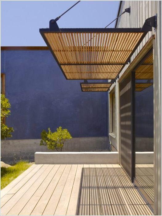 Устойчивый к погодным условиям деревянный козырек отлично подойдет для современного загородного дома.
