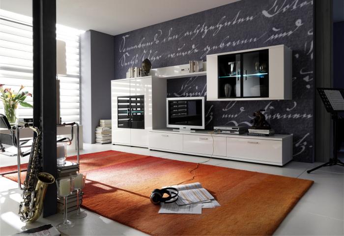 Современный дизайн просторной гостиной комнаты, оформленной в светло-серых тонах, с натуральным оранжевым ковром и белоснежной модульной стенкой.
