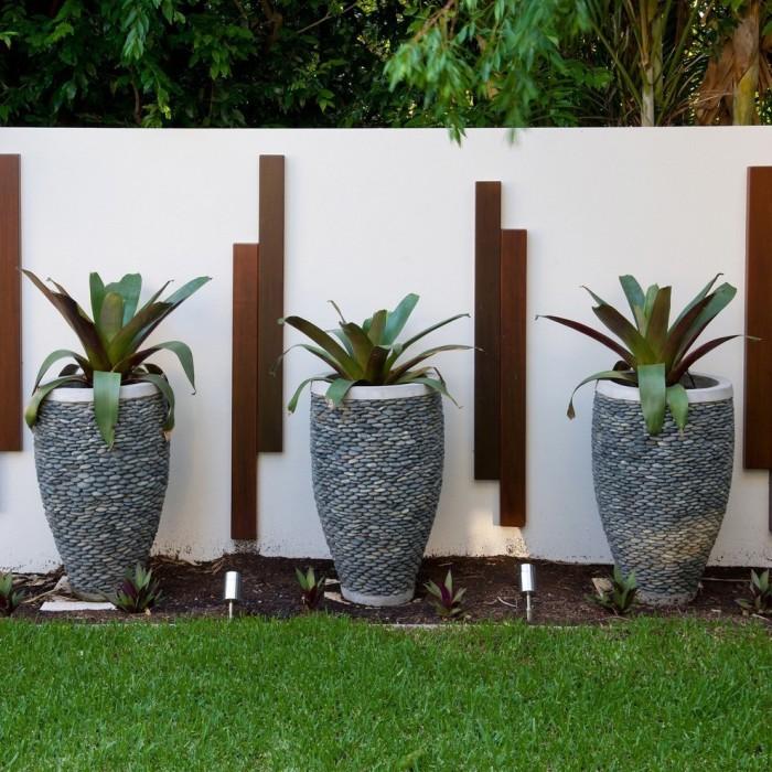 Три однакових кашпо циліндричної форми, зроблені з цільного каменю, і декоровані дрібною галькою.