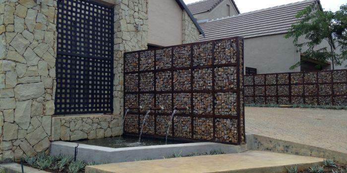 Многофункциональная сетчатая конструкция, которая выполняет роль забора и декоративного водопада.
