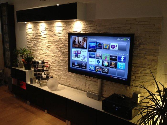 Стена, украшенная декоративной каменной плиткой в зоне для просмотра телевизора.