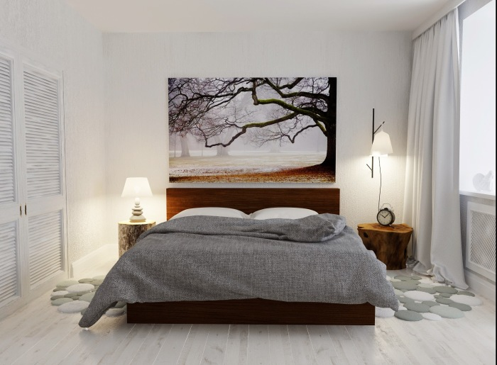 Спальная комната с большой картиной над спальным местом.